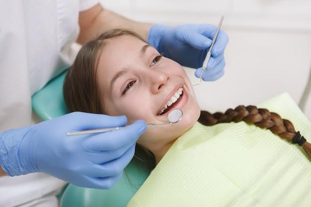 Close up van een mooi gelukkig jong meisje glimlachend terwijl tandarts haar tanden onderzoekt