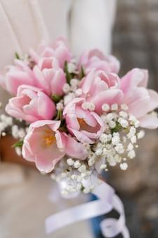 Close-up van een mooi huwelijksboeket van roze witte tulpen in de handen van de bruid. hoge kwaliteit foto