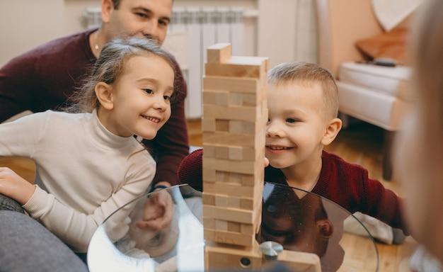 Close up van een mooi klein kind spelen met zijn zus in een familiespel samen met hun ouders thuis lachen.