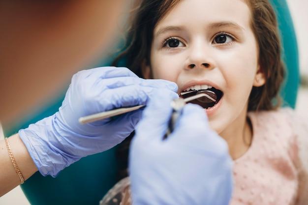 Close up van een mooi klein meisje, zittend in een stoel stomatologie met mond geopend tijdens een tandonderzoek door een pediatrische tandarts.
