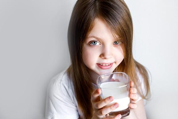 Close-up van een mooi meisje dat een witte melk in een glas houdt en kijkt
