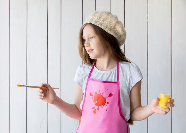 Close-up van een mooi meisje die gele verf en penseel houden die in hand zich tegen houten muur bevinden