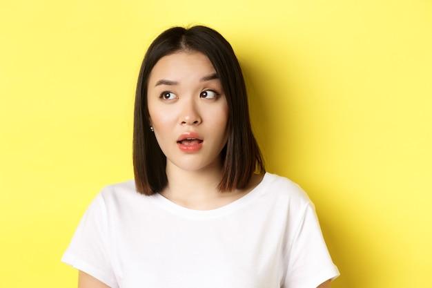 Close-up van een mooie aziatische vrouw met een schone, perfecte huid, een wenkbrauw optrekkend en naar links kijkend met een geïntrigeerd gezicht, staande over een gele achtergrond.