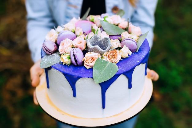 Close-up van een mooie blauwe cake die een meisje houdt. ongelooflijke decoraties met rozen en bitterkoekjes