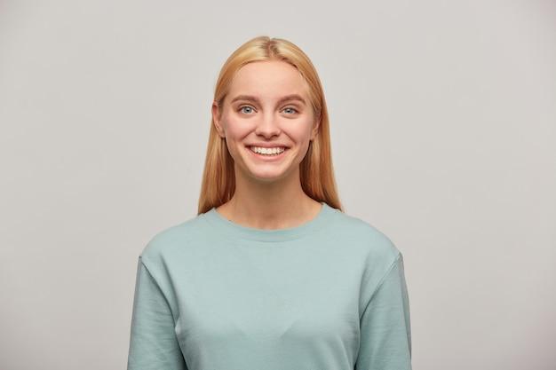 Close-up van een mooie blonde jonge vrouw met lang haar naar beneden, op zoek blij blij lachend