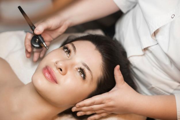 Close up van een mooie brunette met zuurstof procedure op haar gezicht in een wellness-spa salon.