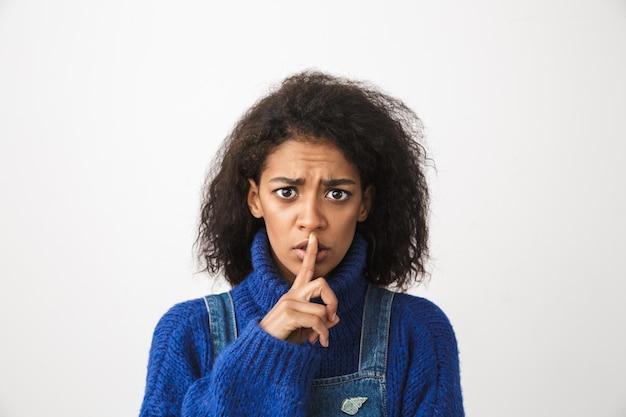 Close-up van een mooie jonge afrikaanse vrouw, gekleed in trui staande geïsoleerd, stilte gebaar tonen