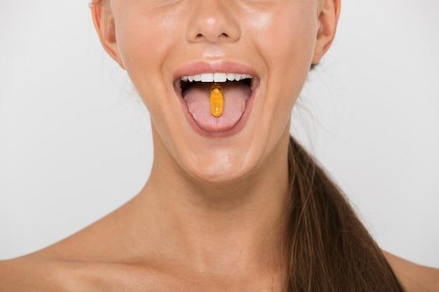 Close-up van een mooie jonge topless vrouw geïsoleerd, pil capsule op haar tong te houden