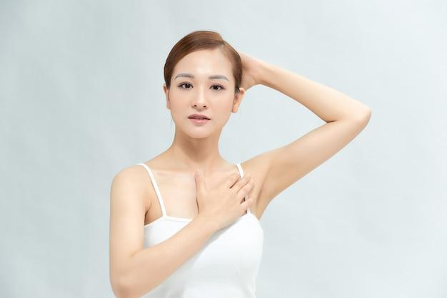 Close-up van een mooie jonge vrouw die haar gladde oksel toont geïsoleerd op een witte achtergrond
