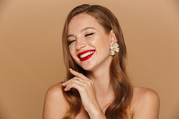 Close-up van een mooie jonge vrouw, gekleed in make-up en juwelentoebehoren poseren geïsoleerd over beige muur