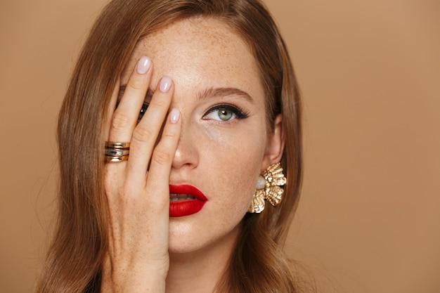 Close-up van een mooie jonge vrouw, gekleed in make-up en sieraden accessoires poseren geïsoleerd over beige muur, met de hand op haar gezicht