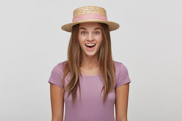 Close-up van een mooie jonge vrouw in een strooien hoed met een roze lint kijkt opgetogen blij verbaasd