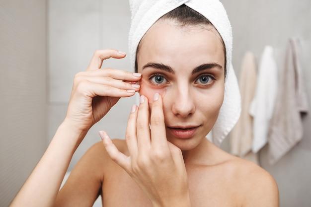 Close up van een mooie jonge vrouw met handdoek op haar hoofd staan in de badkamer, oog patches toe te passen