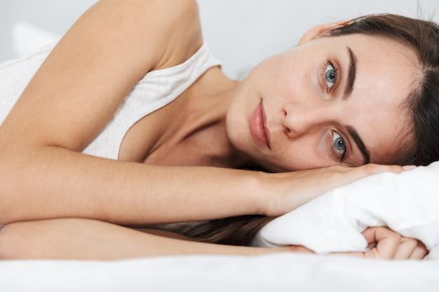 Close up van een mooie jonge vrouw ontspannen op bed thuis