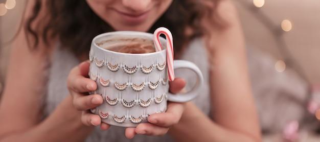 Close-up van een mooie kerstkop in vrouwelijke handen op een onscherpe achtergrond.
