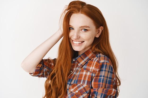 Close-up van een mooie roodharige tienervrouw die natuurlijk rood haar aanraakt, lacht met witte tanden en er gelukkig uitziet, studiomuur