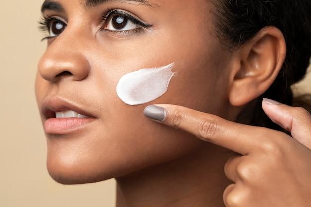 Close-up van een mooie vrouw die een vochtinbrengende crème gebruikt voor huidverzorgingsroutine