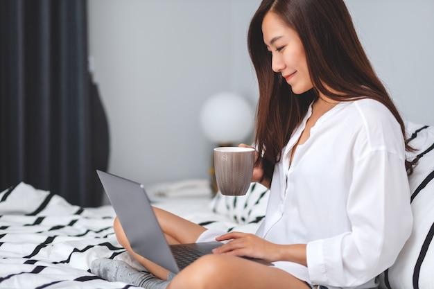 Close-up van een mooie vrouw die en aan laptop computer gebruiken werken, koffie drinken terwijl thuis het zitten op een wit comfortabel bed