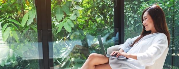Close-up van een mooie vrouw die en op laptop computer werkt typen terwijl het zitten op een witte leunstoel thuis met groene aard