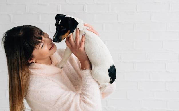 Close-up van een mooie vrouw die haar hond jack russell terrier kust op een witte achtergrond. het concept van een zorgzame eigenaar en huisdier