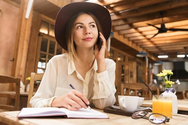 Close up van een mooie vrouw in hoed zittend aan de café tafel