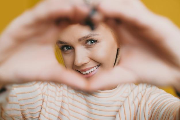Close-up van een mooie vrouw lachend terwijl het kijken door een hart gedaan door haar handen geïsoleerd op gele muur.