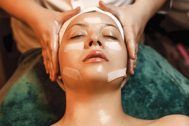 Close up van een mooie vrouw leunend met gesloten ogen ina spa bed rusten terwijl het doen van huidverzorging routine.