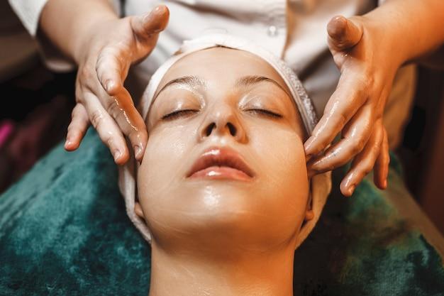 Close up van een mooie vrouw met huidverzorging routine in een wellness-kuuroord.