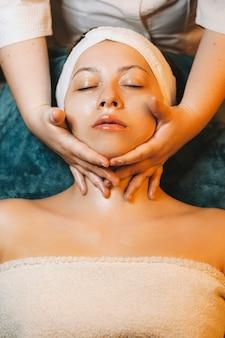 Close-up van een mooie vrouw met nekmassage terwijl ze de routine van de gezichtshuid doet in een wellnesscentrum.