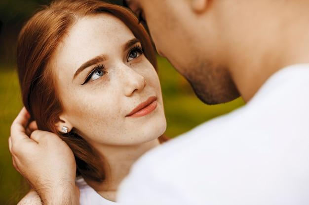 Close up van een mooie vrouw met rood haar en sproeten kijken lachend naar haar vriendje buiten.