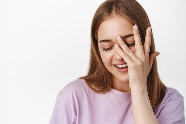 Close-up van een mooie vrouw raak zachtjes haar gezichtshuid aan, bedek het gezicht met de hand, kijk naar beneden koket en flirterig, glimlachend, witte muur