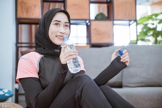 Close-up van een moslimvrouw die een hijab-gymkleding draagt, zit op de grond met een drinkwaterfles in de woonkamer
