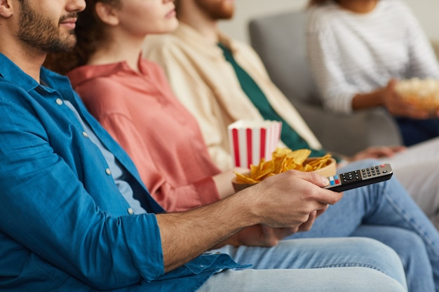 Close up van een multi-etnische groep vrienden samen tv kijken zittend op een gezellige bank thuis en genieten van snacks