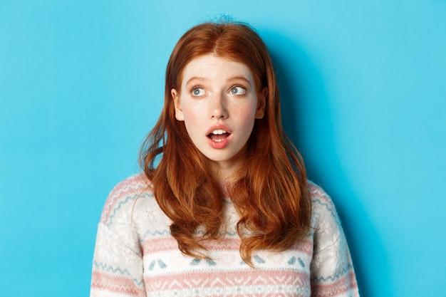 Close-up van een onder de indruk roodharig meisje dat verbaasd naar links staart, met open mond vol ontzag en een blik werpt op promo, staande in de wintertrui tegen een blauwe achtergrond.