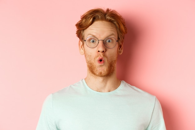 Close-up van een onder de indruk roodharige man met een bril die wow zegt, de wenkbrauwen verbaasd optrekt en naar de camera staart, staande over een roze achtergrond.