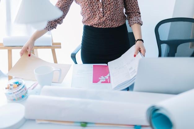 Close-up van een onderneemster die een geopend dossier op bureau houdt