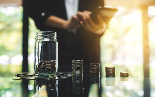 Close-up van een onderneemster die met muntstukkenstapel berekent en een kruik van het glasgeld voor besparing en financieel concept