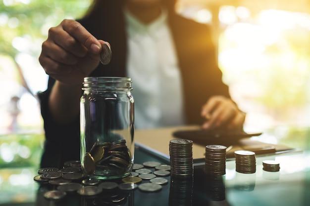 Close-up van een onderneemster die muntstukken in een glaskruik zetten, en geld voor besparing en financieel concept berekenen stapelen