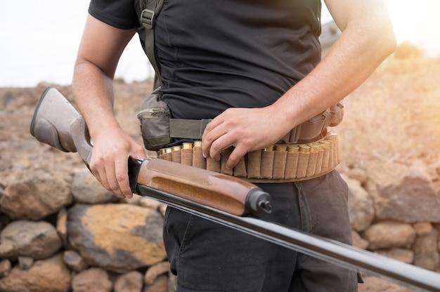 Close-up van een onherkenbare jager, die een jachtgeweer laadt, een jachtgeweer en munitie in zijn hand houdt.