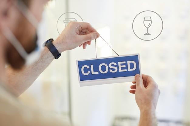 Close-up van een onherkenbare man die een gesloten bord op de glazen deur van café hangt, covid-beperkingen concept, kopieer ruimte
