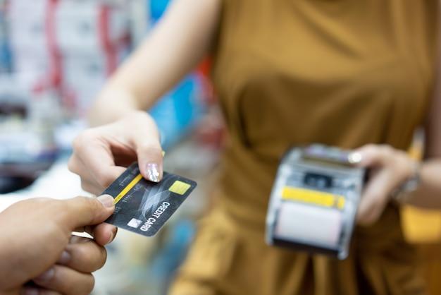 Close-up van een onherkenbare persoon die een betaling aan een barman verricht door middel van een creditcard in een bierbrouwerij gedurende de dag