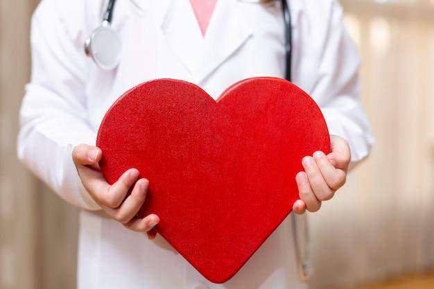 Close-up van een onherkenbare persoon in de jurk van de dokter met een groot hart in zijn handen
