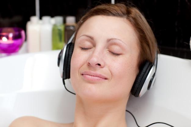 Close-up van een ontspannen jonge vrouw het luisteren muziek in een schuimbad