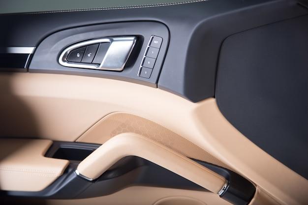 Close-up van een open beige deur van een moderne luxeauto onder de lichten