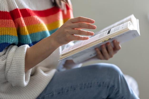 Close-up van een open boek in de handen van een meisje in een felgekleurde trui.