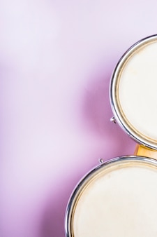 Close-up van een opgeheven mening van bongotrommel op purpere achtergrond