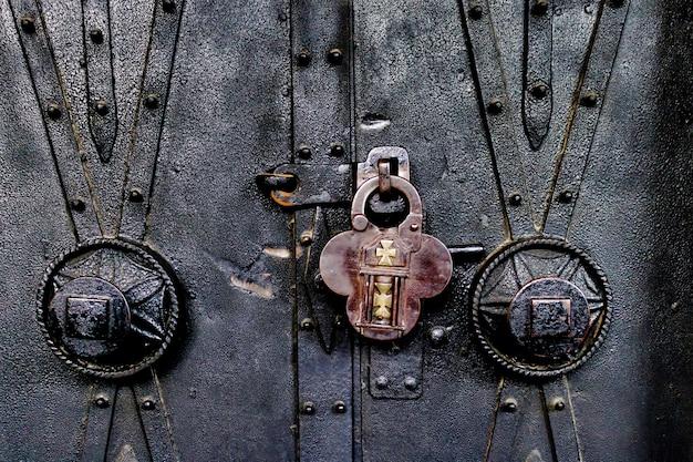 Close-up van een oud hangslot op een oude sierlijke kerkdeur