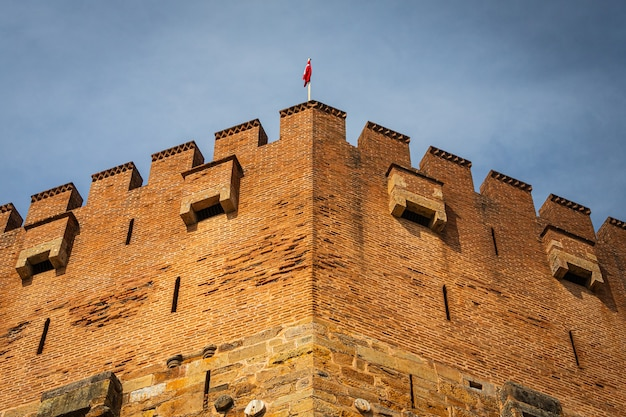 Close-up van een oude rode toren met turiyets vlag. scheepswerf en arsenaal in alanya op een zonnige dag, turkije