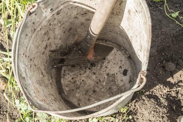 Close-up van een oude vuile roestige ijzeremmer met hark op de achtergrond van grond en gras in de tuin.