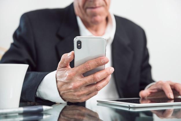 Close-up van een oudere man slimme telefoon in de hand te houden